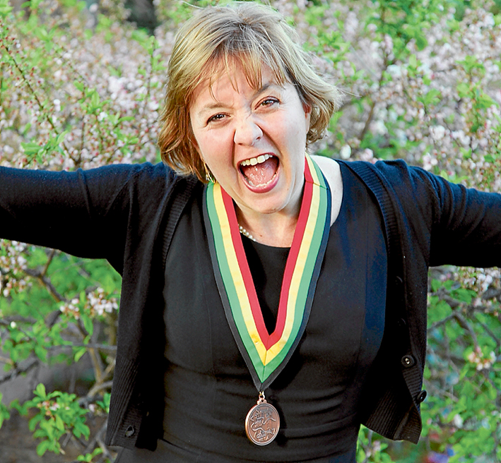 Honoured citizen: Luz Restrepo shows her joy last October after receiving the St Michael's medallion in recognition for her work in helping prevent violence, trauma and destructiveness or promotes growth, health and wellbeing.