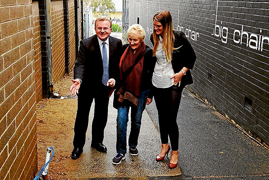 Hasten slowly: Federal MP Bruce Billson, Judy Edwards and Kim Rowe of Mornington Chamber of Commerce inspect CCTV and lighting wiring in one of the laneways between Main St and McLaren Place. Poles were installed last week. Picture supplied