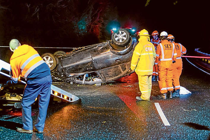 Crash scene: SES and CFA crews attempt to right the upturned car on Nepean Hwy before it is towed away. Picture: Gary Sissons