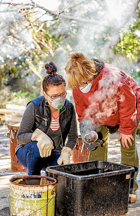 All fired up: Ceramicists Ev Burton, left, and Sue Sanderson practice the ancient art of raku at Rye. Picture: Yanni