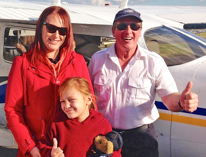 Flying high: Peter Moran and passengers Kyla, 8, and mum Tamara, at Bankstown after their Angel Flight from Hillston, NSW.