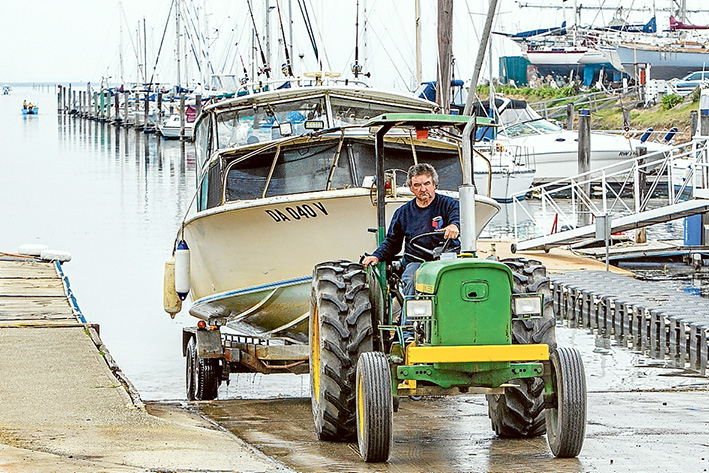 Fishing trip gone wrong: Rescuer Howard Fisher's cabin cruiser is brought ashore at Yaringa harbour, Sunday morning. Picture: Gary Sissons