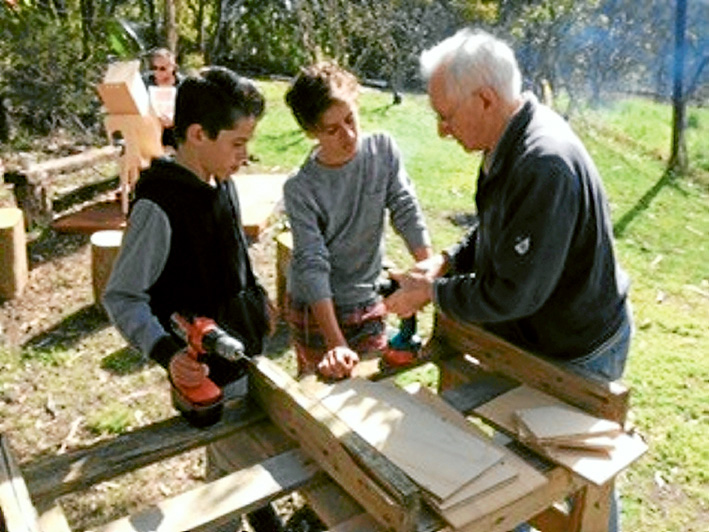 Boxing lesson: Richard from Mornington Men's shed helping Flynn and Trinity build a nesting box.
