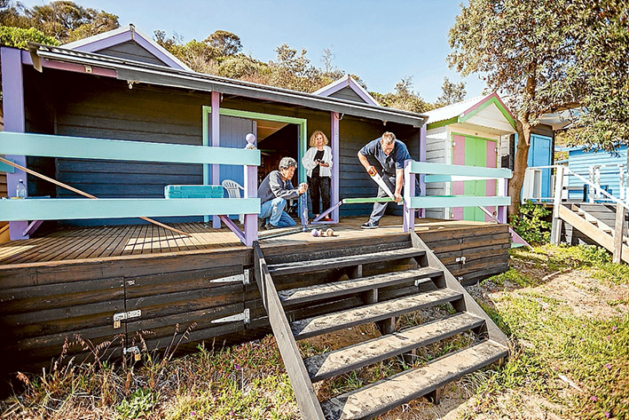 Wilful damage: Mt Martha bathing box owners Derek and Wendy Leong count the cost as carpenter Iain Proudfoot makes repairs. Picture: Yanni