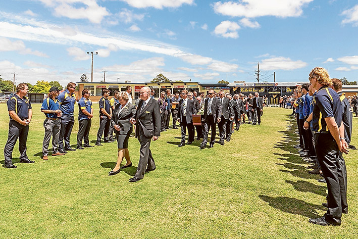 Ground of honour: Leanne Gomm and funeral director Ted Bull lead the funeral procession for her husband Murray Gomm through a guard of honour at Somerville Football Oval on Monday. Picture: Gary Sissons