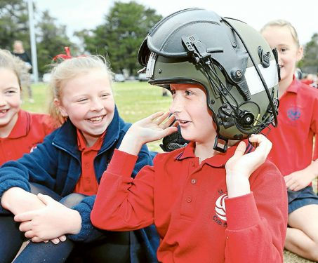 Madison Cruickshank of St Josephs Primary Schools tries on a pilots helmet during 723 Squadron visit to Cyril Fox Reserve, Crib Point, Victoria.
