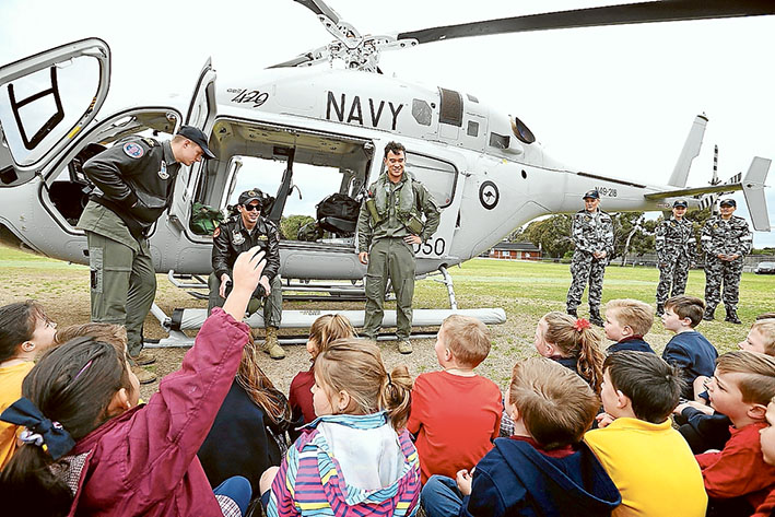 Looking good: St Joseph's pupil Madison Cruickshank, below, tries on a helicopter pilot's helmet during the Navy 723 Squadron visit to Cyril Fox Reserve, Crib Point. Above, Sub Lieutenant Frank Tachibana (right), Lieutenant Tristram Gleeson (centre) and Sub Lieutenant Olie Bohling fielding questions from Crib Point Primary pupils.