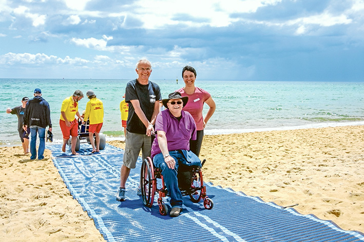 Available to all: Bill Hallett and Virginia Richardson show Mark Hopper how to best use the wheelchair-friendly plastic matting being trialled by Mt Martha Life Saving Club.